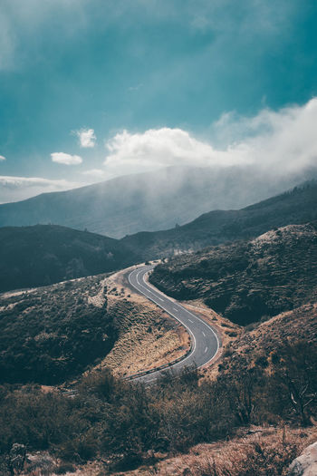 Aerial view of mountain road against cloudy sky
