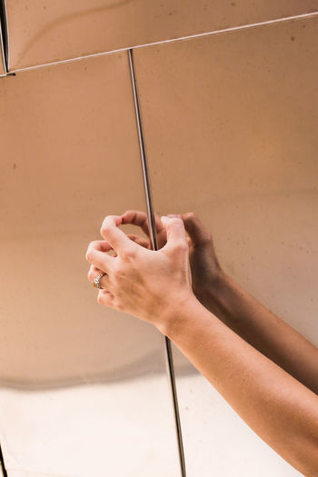 Cropped hand of woman touching metal wall