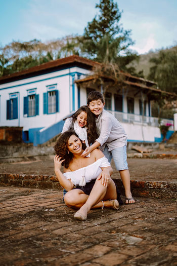 Portrait of smiling mother with son and daughter against building