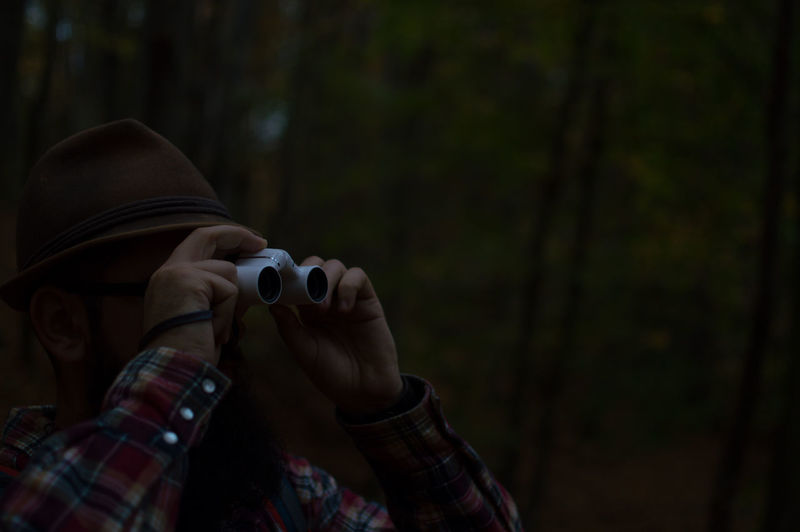 Close-up of man looking through binoculars in forest