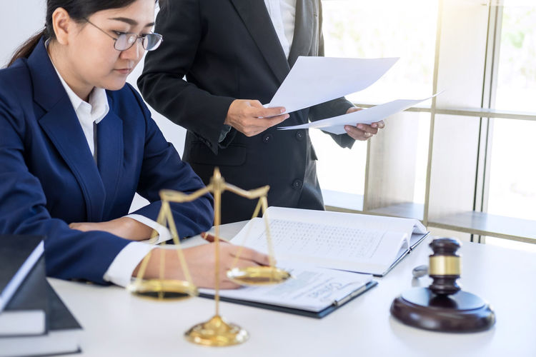 Midsection Of Judge Holding Documents While Colleague Sitting At Table