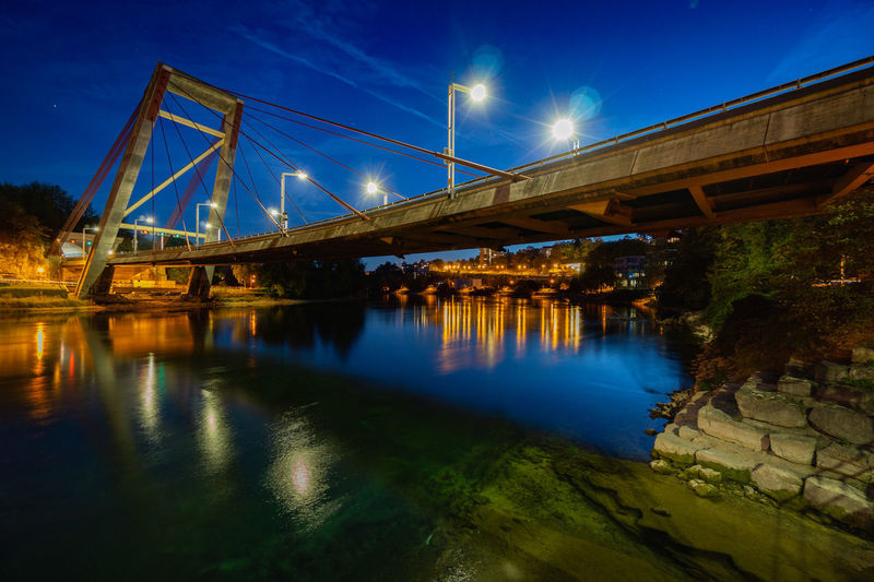 Bridge over river against sky at night