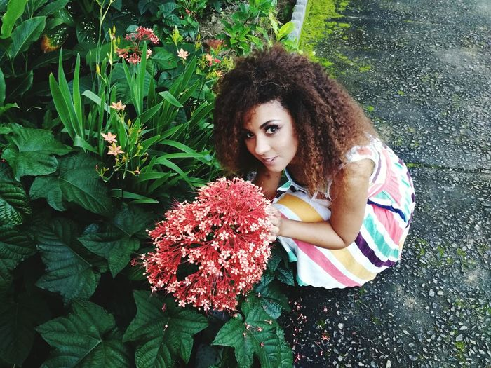 Portrait of beautiful woman by red flowering plants