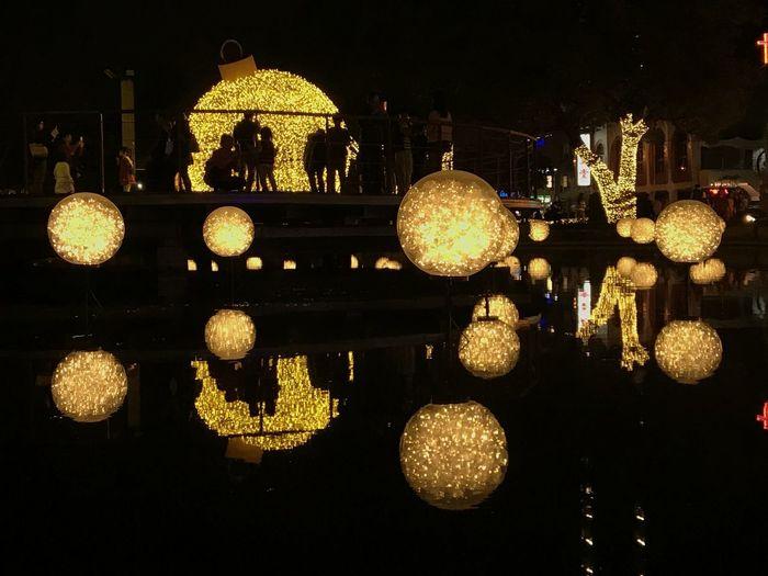 Illuminated lighting equipment hanging on bridge over city at night
