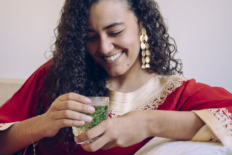 Smiling young woman holding drink at home