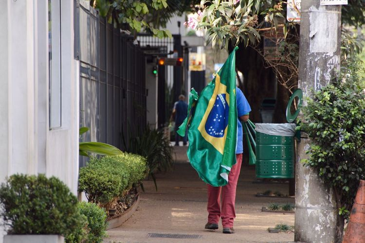 Street Photography World Cup World Cup 2018 City Life Streetphotography Flag Clothing Building Exterior One Person Traditional Clothing Full Length Green Color Celebration Outdoors Plant Day Nature Built Structure Real People Rear View Walking Traditional Clothing Green Color