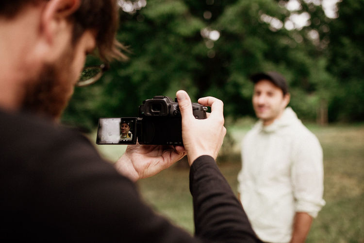Midsection of man photographing with mobile phone