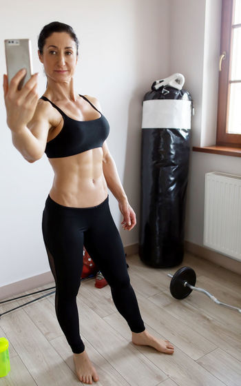 Muscular woman taking selfie while standing against wall