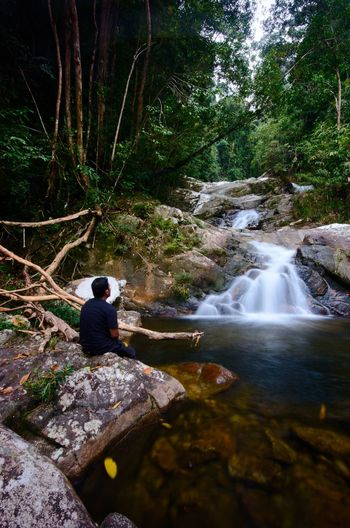 Wallpaper Background Malaysia ASIA Tree Water Sitting Forest Men Waterfall Flowing Water Hiker Hiking Pole Power In Nature Backpack Hiking Flowing Rock Formation Long Exposure