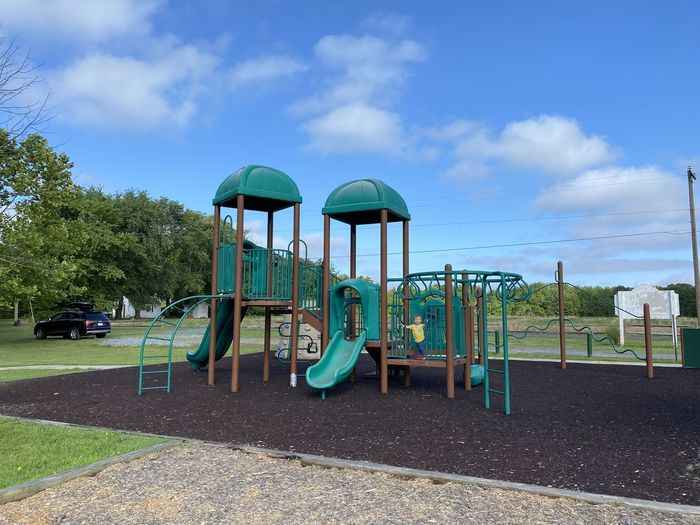 View of playground in park against blue sky