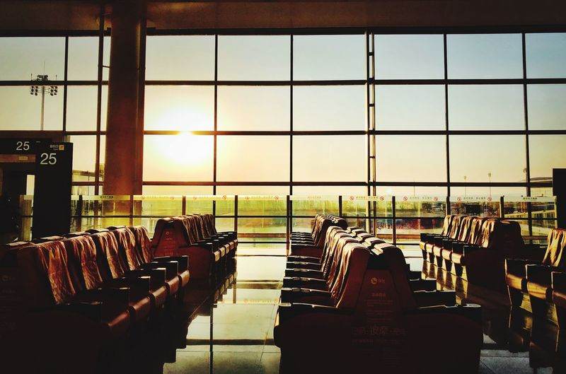 Empty chairs at airport against sky during sunset