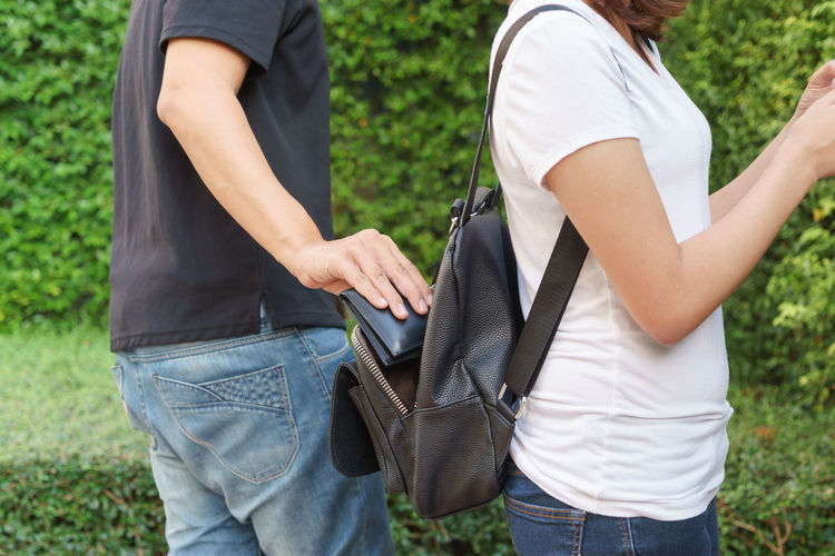 Midsection of man stealing purse from woman bag