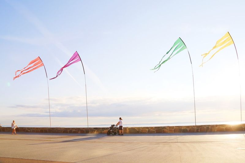 Low angle view of flags on road amidst field against sky