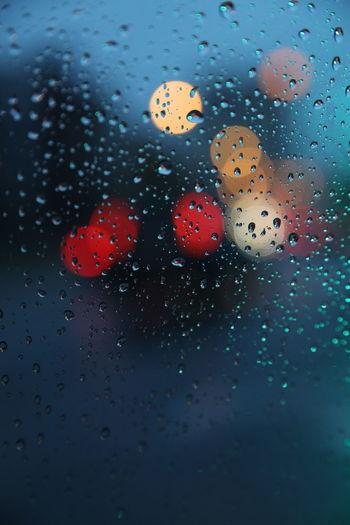 Close-up of raindrops on car window at dusk