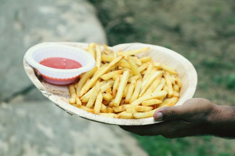 Close-up of hand holding french fries