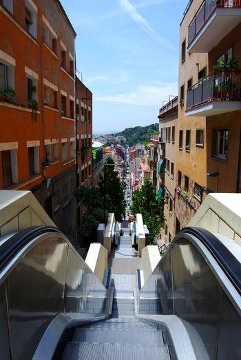 Escalator amidst buildings against sky