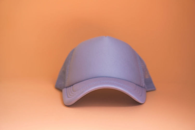 Close-up of hat on table against orange background