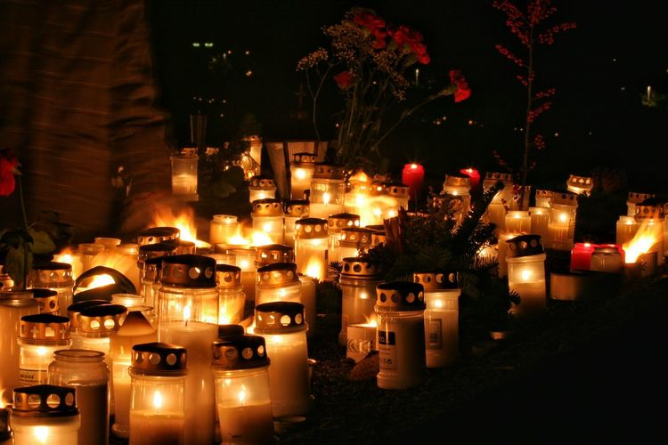 Lit candles at cemetery during night