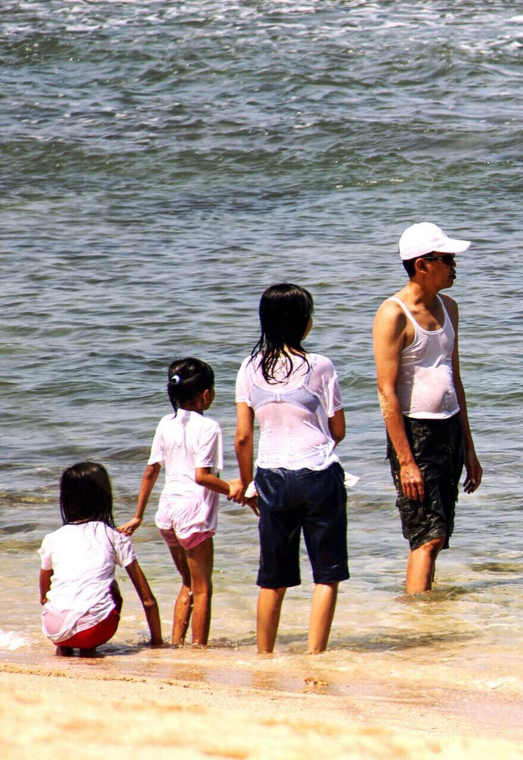 water, togetherness, lifestyles, bonding, leisure activity, love, rear view, family, friendship, person, girls, men, childhood, boys, vacations, full length, casual clothing, sea