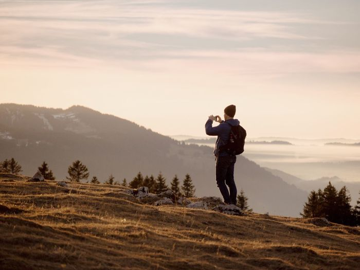 Backpacker photographing while standing on mountain against sky during sunset