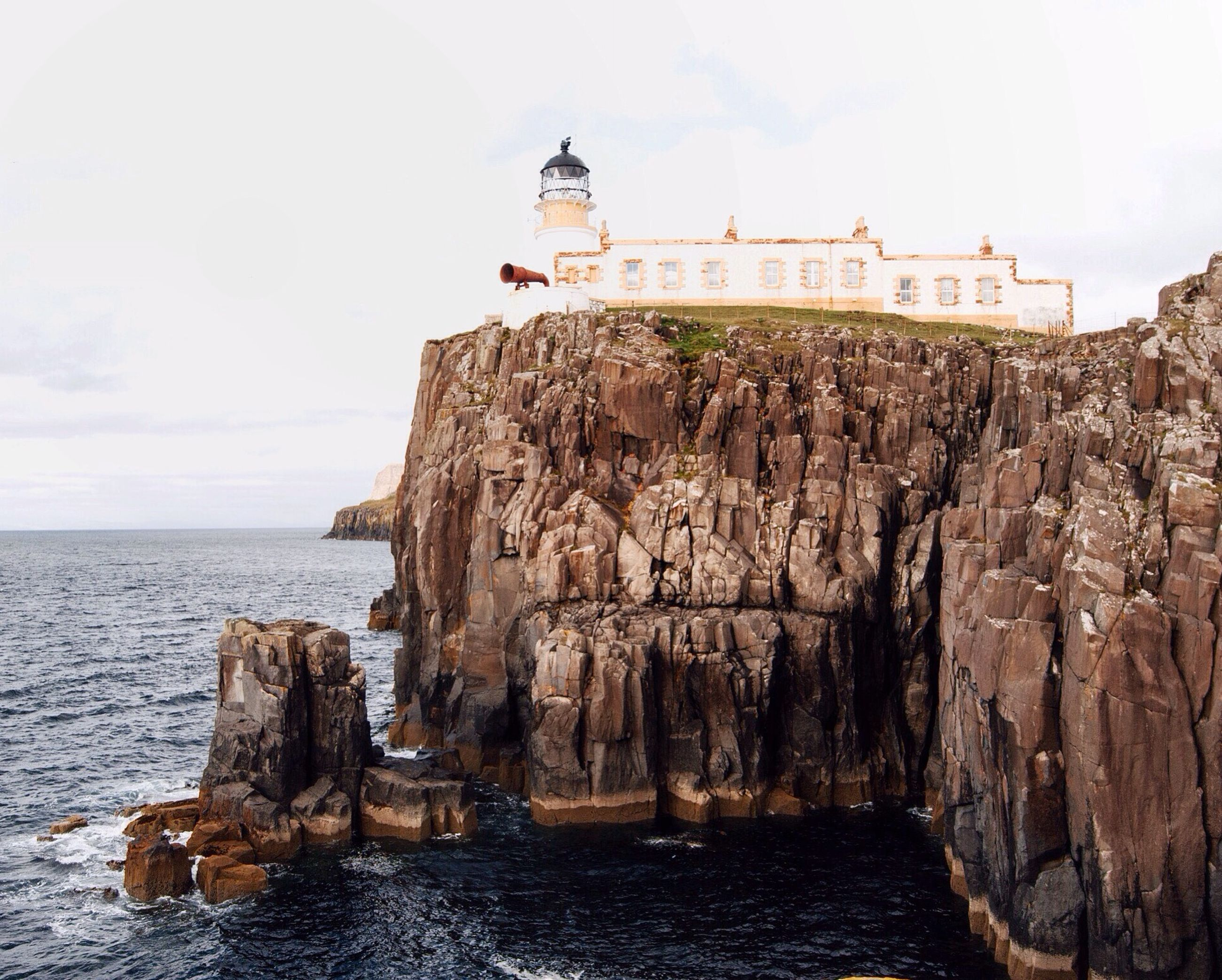 sea, water, horizon over water, sky, built structure, architecture, rock - object, building exterior, tranquil scene, lighthouse, tranquility, nature, scenics, rock formation, rock, cliff, beauty in nature, outdoors, day, beach