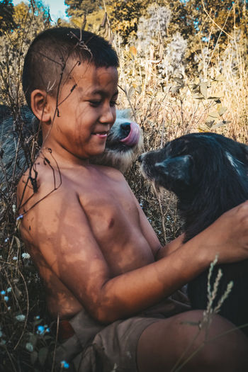 Shirtless boy playing with dogs while sitting against plants