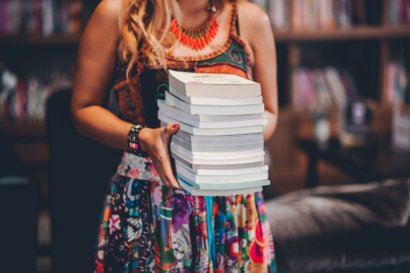Midsection of woman holding book in library