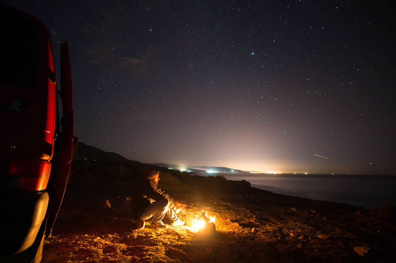 Man Sitting By Campfire On Mountain Against Sky At Night
