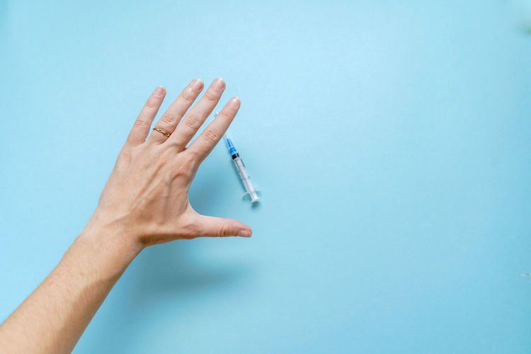 Close-up of hand holding blue background