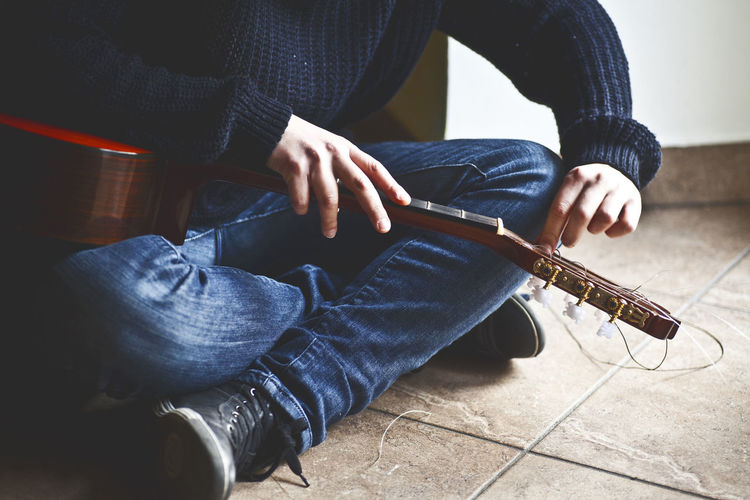 Low Section Of Man Removing Guitar Strings