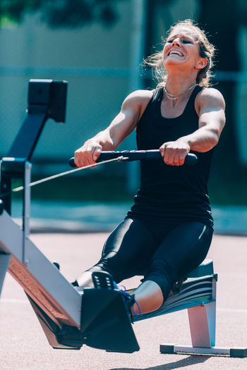 Woman exercising in gym during sunny day