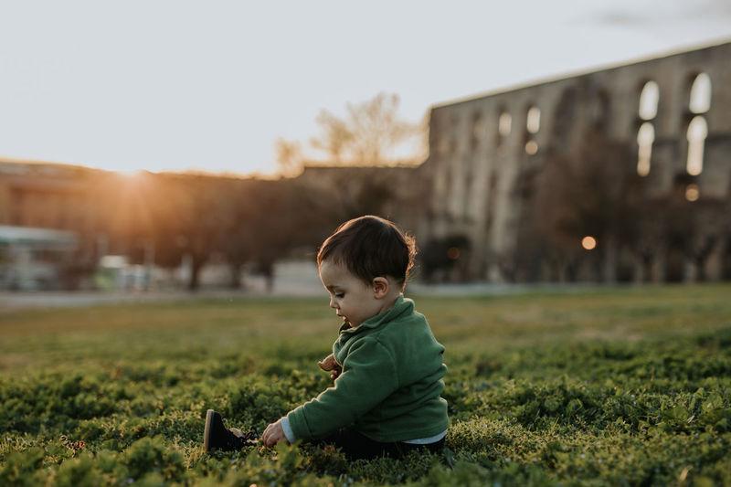 Side view of a boy sitting on field