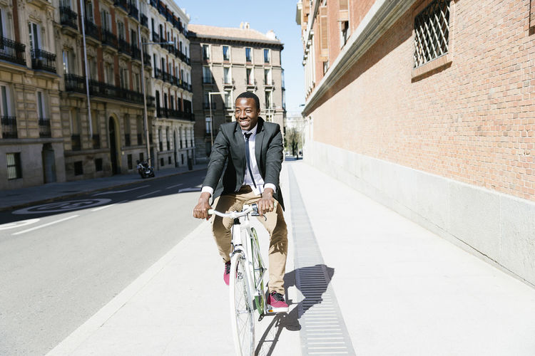 Smiling businessman cycling on bicycle in city