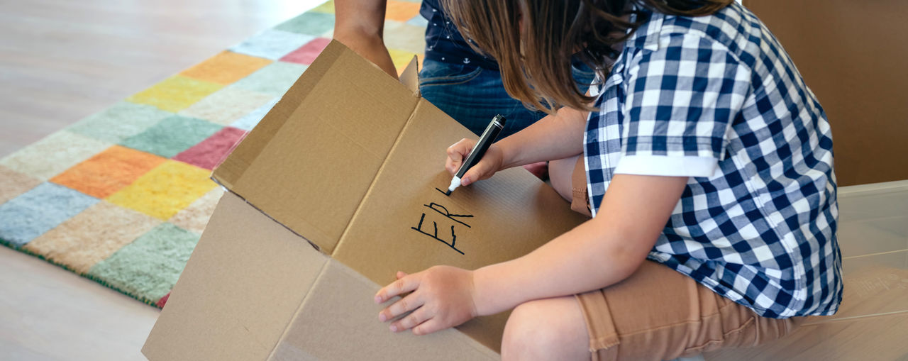 Little boy writing his name in a moving box with his father Family Fun Happiness Happy Horizontal Man Moving Unpacking Writing Boxes Boy Cardboard Home Interior House Indoors  Kid Lifestyles Living Room New Home Packing Painting Placing Real People Relocating Two People