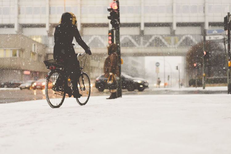 Woman on bicycle in snow covered city