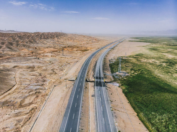 Aerial view of roads amidst field and arid landscape against sky