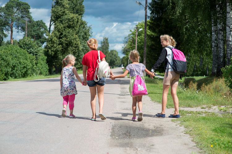 Rear view of children walking on road