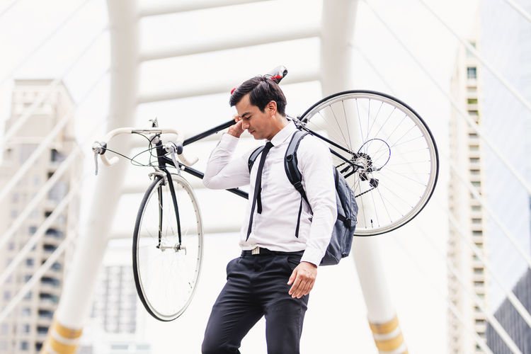 Man standing by bicycle