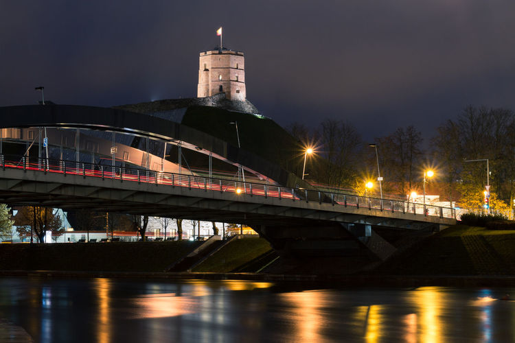 View of bridge over river at night