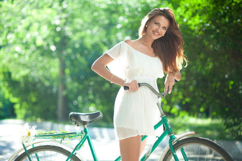 Beautiful young woman in a white summer dress holding on to bike Riding Outdoors Hair Real People Standing Adult Transportation Hairstyle Portrait Emotion Happiness Land Vehicle Day Beautiful Woman Lifestyles Women Casual Clothing Young Adult One Person Bicycle Three Quarter Length Smiling Leisure Activity Focus On Foreground Young Women Front View Looking At Camera