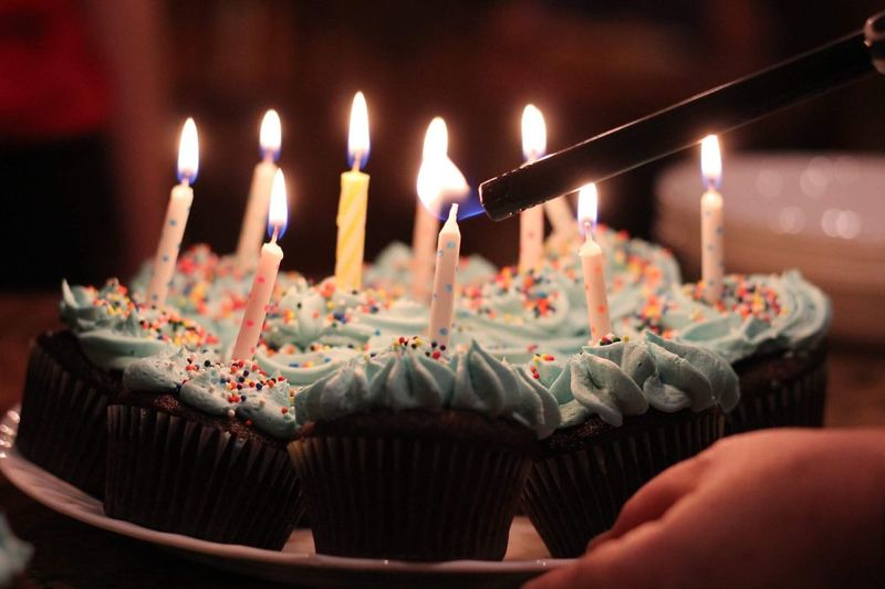 Cropped Hand Igniting Birthday Candles On Cupcakes In Darkroom