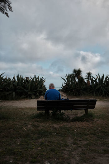 Rear view of man sitting on bench on field against sky