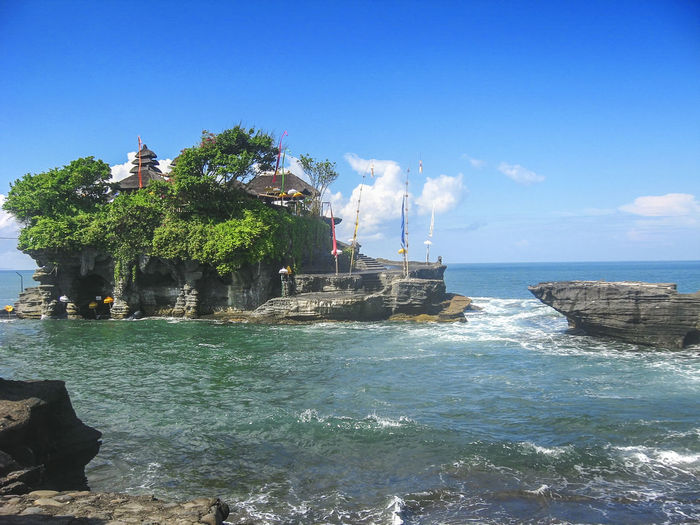 Tanah Lot Temple in Bali Indonesia - nature and architecture background ASIA Bali, Indonesia Holiday Architecture Backgrounds Beach Beauty In Nature Blue Blue Sky Built Structure Day Nature No People Outdoors Rock - Object Sea Sky Sunlight Tanah Lot Temple Traditional Travel Destinations Tree Vacation Water