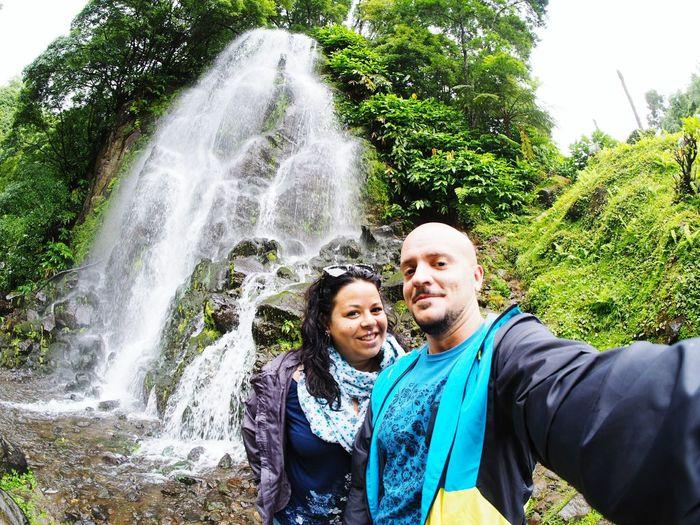 Portrait of happy friends against waterfall