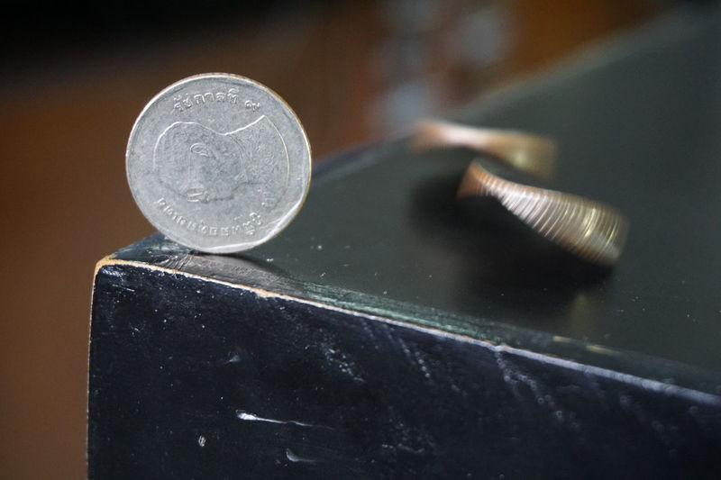 The Thai baht currency coin on the table in a vertical position with a moving coin. Business Close-up Coin Coins Day Economic Economy Fluctuation Forestation Indoors  No People Risks Uncertain Volatile