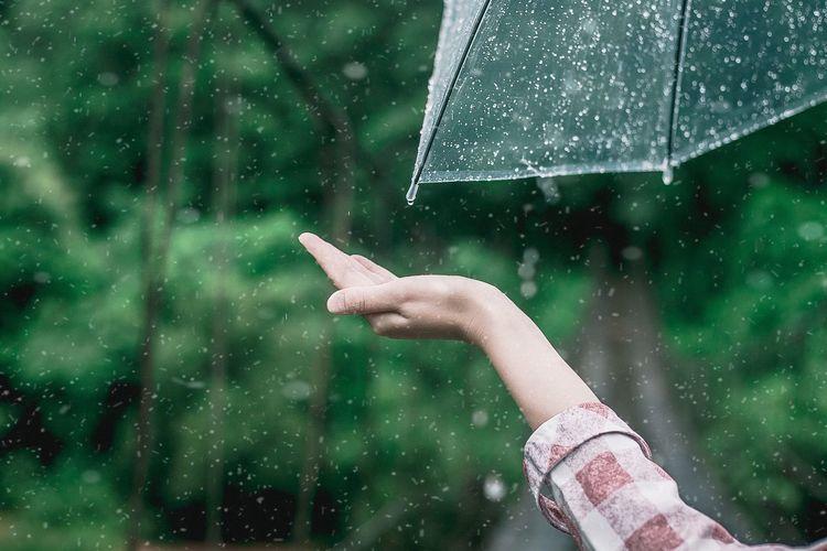 Hand holding wet glass during rainy season