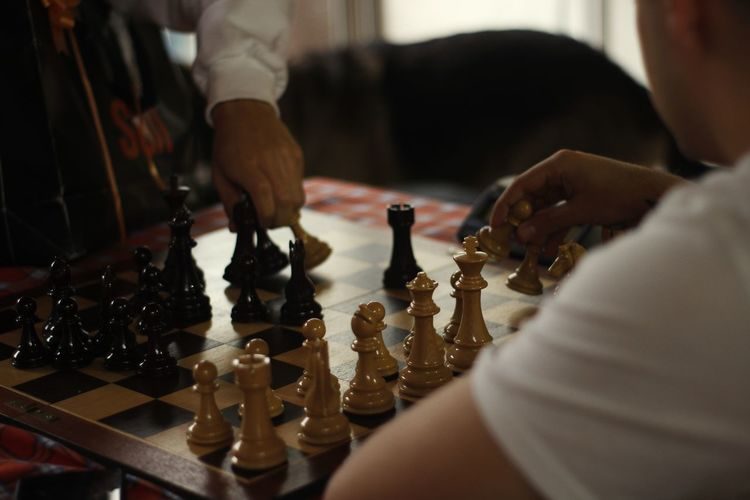 Midsection of people playing chess