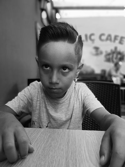 Boy looking away while sitting at table