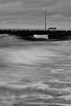 Bench on a pier shot at dawn with long exposure Autumn Wind Bench Empty Bench Rough Nature Beauty In Nature Black And White Cloud - Sky Cold Atmosphere Cold Temperature Crashing Waves  Dark Atmosphere Day Mystery Nature No People Outdoors Sea Sky Storm Clouds Storm Weather Water Waterfront Waves Windy Day