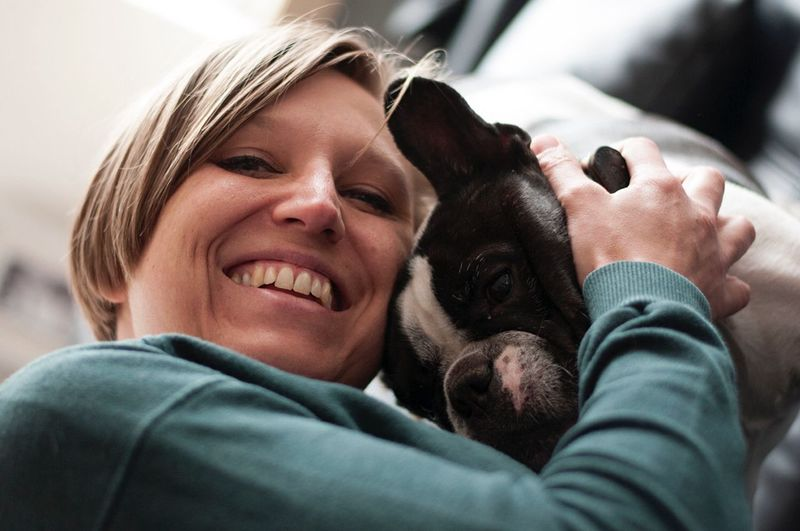 Low Angle Portrait Of Smiling Woman With French Bulldog